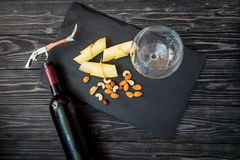 Bottle of red wine, appetizers and corkscrew on wooden background.  Royalty Free Stock Photography
