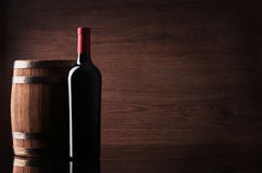 Bottle of red wine and barrel. On dark background royalty free stock photos