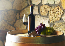Bottle or red wine on a barrel Stock Image