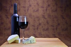 A bottle of red wine and cheese. A bottle and glass of red wine with two types of cheese Royalty Free Stock Images