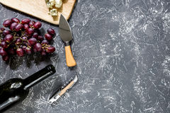 Bottle of red wine with cheese and grape aperitive on grey stone table background copyspace top view. Bottle of red wine with cheese and grape aperitive on grey Royalty Free Stock Images