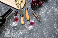 Bottle of red wine with cheese and grape aperitive on grey stone table background copyspace top view. Bottle of red wine with cheese and grape aperitive on grey Royalty Free Stock Photos