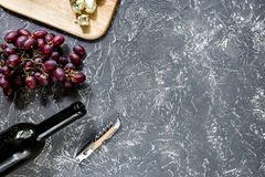 Bottle of red wine with cheese and grape aperitive on grey stone table background copyspace top view Stock Photos