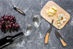 Bottle of red wine with cheese and grape aperitive on grey stone table background top view. Bottle of red wine with cheese and grape aperitive on white Royalty Free Stock Photos