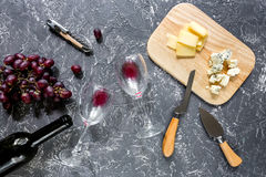Bottle of red wine with cheese and grape aperitive on grey stone table background top view. Bottle of red wine with cheese and grape aperitive on white Stock Photos