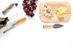 Bottle of red wine with cheese and grape aperitive on white background space for text top view. Bottle of red wine with cheese and grape aperitive on white Stock Photography