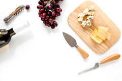 Bottle of red wine with cheese and grape aperitive on white background space for text top view. Bottle of red wine with cheese and grape aperitive on white Stock Image