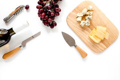 Bottle of red wine with cheese and grape aperitive on white background space for text top view. Bottle of red wine with cheese and grape aperitive on white Stock Photos