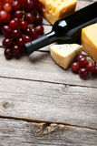 Bottle of red wine, cheeses and grapes on a grey wooden background Royalty Free Stock Photos