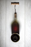 Bottle of red wine with cork on white wooden table Stock Image