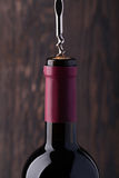 Bottle of red wine and corkscrew Royalty Free Stock Photo