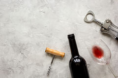 Bottle of red wine and corkscrew on stone background top view mockup Stock Image