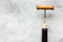 Bottle of red wine with corkscrew on white stone background Stock Photos