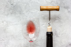Bottle of red wine with corkscrew on white stone background Royalty Free Stock Photography