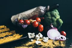 A bottle of red wine, delicious fresh tomatoes cherry and red hot chili peppers in a black dish lying on a wooden Royalty Free Stock Photography
