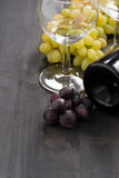 Bottle of red wine, empty glass and grapes on wooden background Stock Image