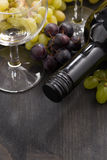 Bottle of red wine, empty glass and grapes on wooden background Stock Photo