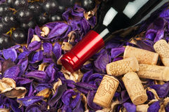 Bottle of red wine on flower petals. Background stock photography