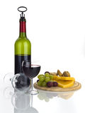 Bottle of red wine with food and glasses isolated on white Royalty Free Stock Photography