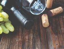 Bottle of red wine with fresh grape and bunch of corks on wooden table stock image