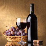 A bottle of red wine, glass. And grapes on a golden background royalty free stock photos