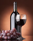 A bottle of red wine, glass. And grapes on a brown background royalty free stock photos