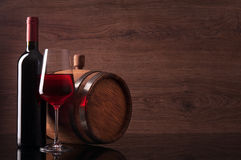 Bottle of red wine, glass and barrel on wooden background. Bottle of red wine, glass and barrel on dark wooden background stock images