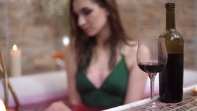 Bottle of red wine with glass are in bath edge. Smiling woman in the background sitting in bath. Lonely lady made romantic night for herself. Focus changes stock video