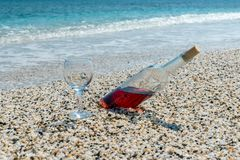 Bottle of red wine with wine glass on the beach at the summer day. Bottle of red wine with wine glass on the beach at the summer sunny day. Sea on the background royalty free stock images