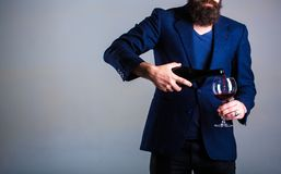 Bottle, red wine glass. Beard man, bearded, sommelier, tasting. Pouring red wine from bottle into the wineglass. Waiter. Pouring red wine in a glas. Sommelier royalty free stock images