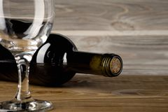 Bottle of red wine with a glass and corkscrew on an old wooden table royalty free stock photos