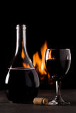A bottle of red wine and a glass in front of a fireplace. Glass and bottle of red wine in front of a fireplace Royalty Free Stock Photography