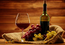 Bottle of red wine, glass and grape in basket in wooden interior Royalty Free Stock Images