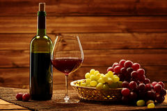 Bottle of red wine, glass and grape in basket in wooden interior Stock Photo