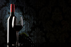 Bottle with red wine and glass on a old stone Royalty Free Stock Images