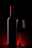 Bottle with red wine and glass on a red gradient Stock Images