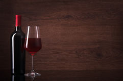 Bottle of red wine and glass. On wooden background royalty free stock photos