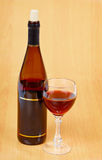 Bottle of red wine and glass on wooden table Stock Photos