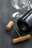 Bottle of red wine, glasses and  corkscrew on wooden background. Bottle of red wine, glasses and  corkscrew on a wooden background, vertical Royalty Free Stock Photography