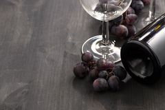 Bottle of red wine, glasses and grapes on a wooden background Stock Images