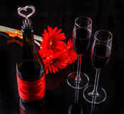 Bottle of red wine, glasses. Bottle of red wine and two wine glasses ,flower on black background Stock Photo