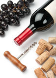 Bottle of red wine, grapes, corkscrew and corks. On white background stock image