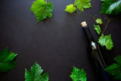 Bottle of red wine, grapes and leaves lying on dark wooden background. Top view. Flat lay. Copy space stock photo
