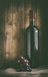 Bottle of red wine with grapes Royalty Free Stock Images