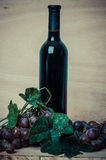 Bottle of red wine and grapes on wood background Royalty Free Stock Photography