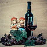 Bottle of red wine and grapes on wood background Royalty Free Stock Photo