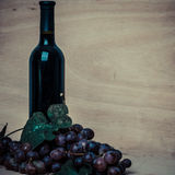 Bottle of red wine and grapes on wood background Stock Images