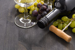 Bottle of red wine and grapes on a wooden background, close-up Royalty Free Stock Photo