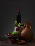 Bottle of red wine, grapes and wooden barrel Royalty Free Stock Images