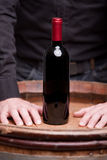 Bottle of red wine and hands of a man Royalty Free Stock Photography